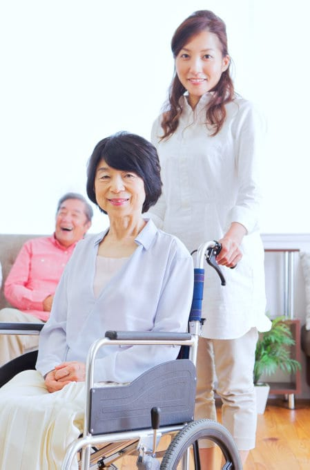 senior woman in a wheelchair and her caregiver