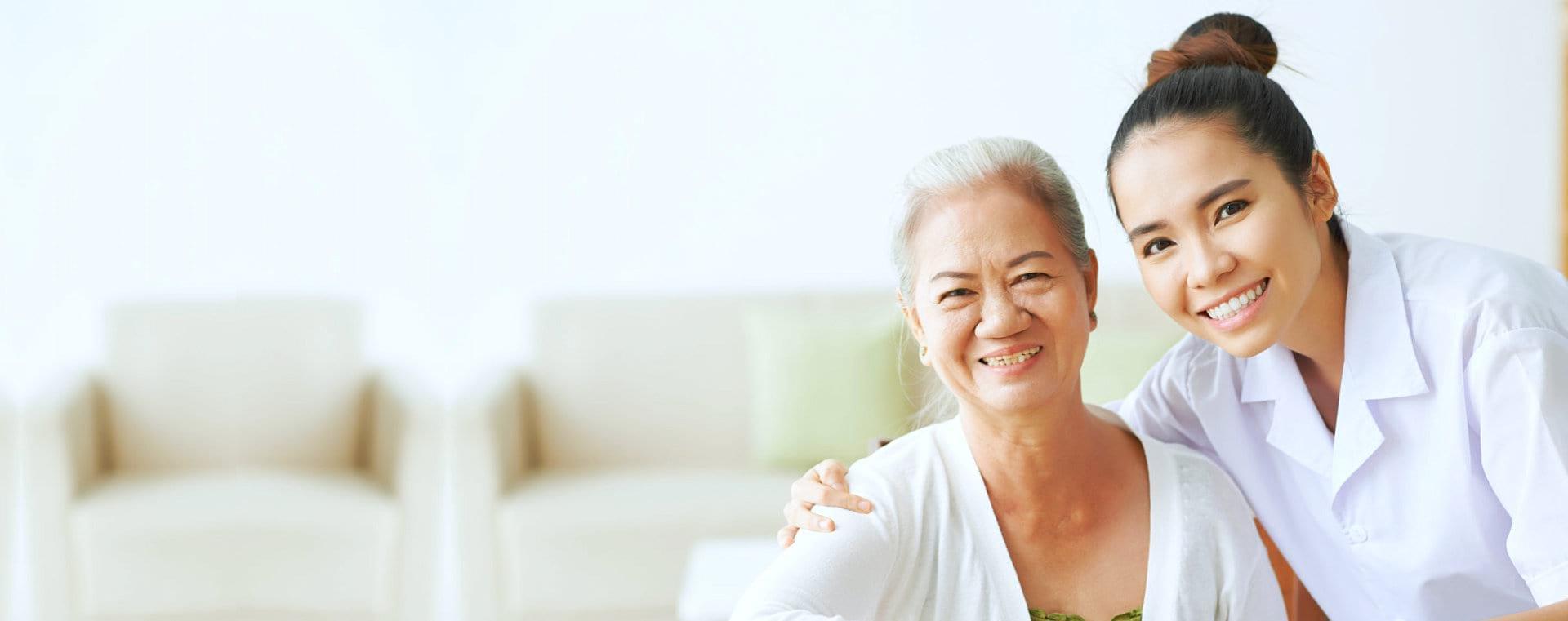 senior and a caregiver smiling