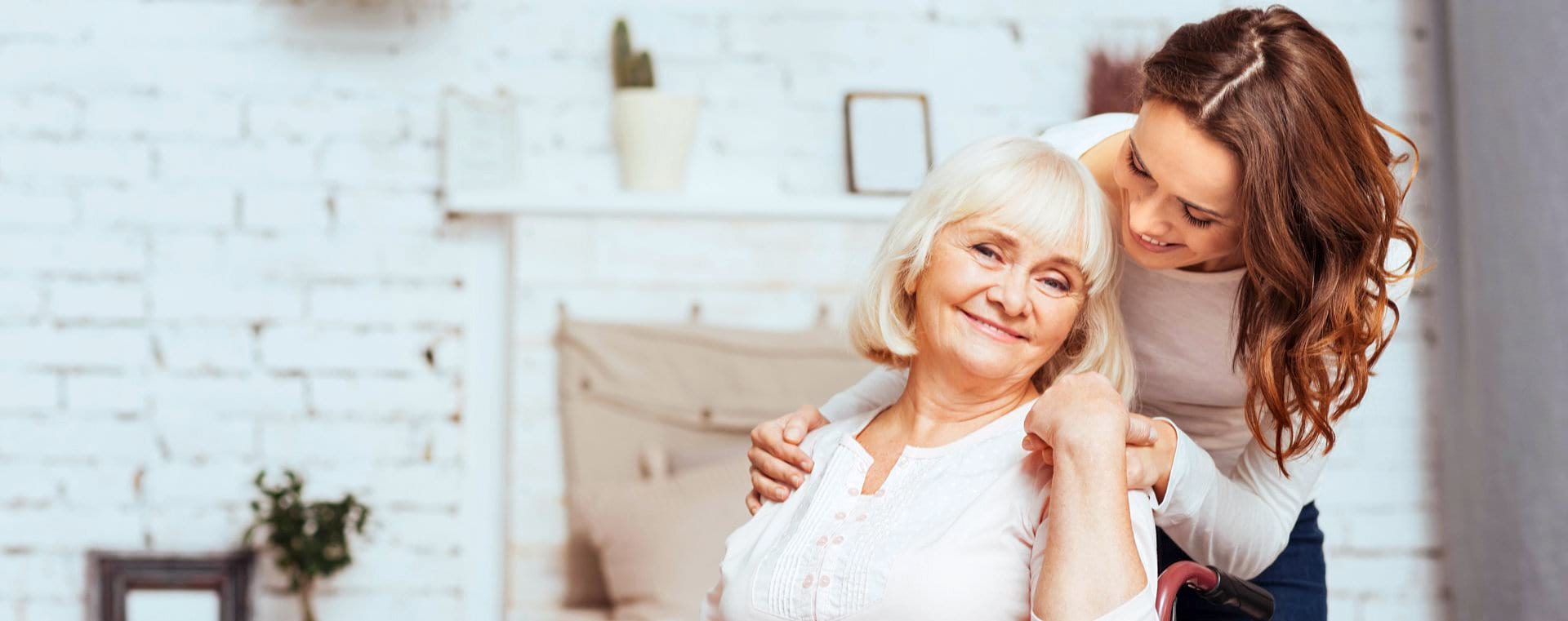 senior in a wheelchair and her caregiver smiling