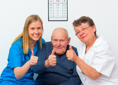 happy moments at the nursing home, senior man showing thumbs up with his caregivers.